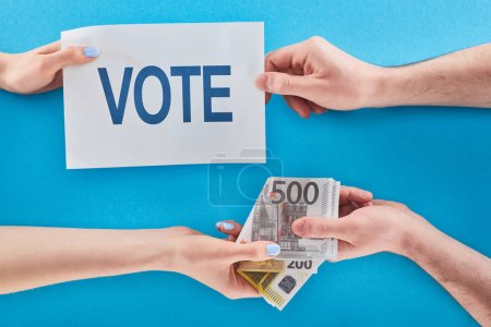 Photo for Partial view of woman giving bribe for vote to man on blue background - Royalty Free Image