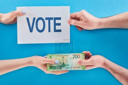 Photo pour Vue partielle de la femme donnant le pot-de-vin pour le vote dans des roubles à l'homme sur le fond bleu - image libre de droit