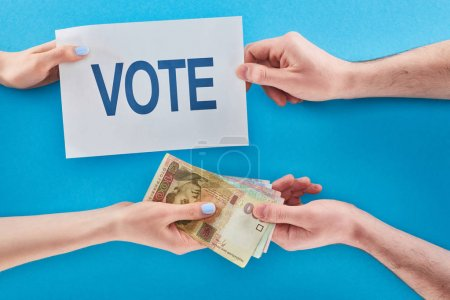 Photo for Partial view of woman giving ukrainian hryvni for vote to man on blue background - Royalty Free Image