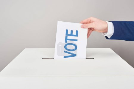 Photo for Partial view of man putting vote in box on grey background - Royalty Free Image