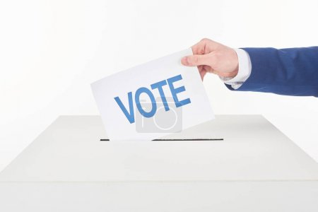 cropped view of man putting card with vote lettering in box isolated on white