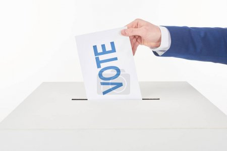 partial view of man putting card with vote lettering in box isolated on white