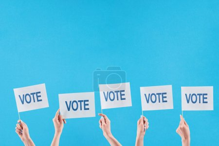 cropped view of women holding flags with vote lettering on blue background