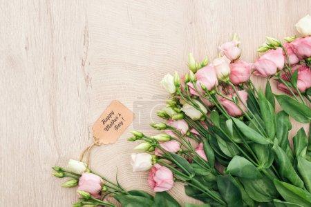 Photo pour Vue supérieure des fleurs d'eustoma avec l'étiquette heureuse de papier de jour de mères sur la table en bois avec l'espace de copie - image libre de droit