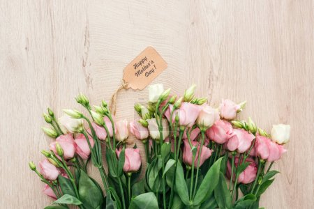 Photo pour Vue supérieure des fleurs d'eustoma avec l'étiquette heureuse de papier de jour de mères sur la surface en bois - image libre de droit