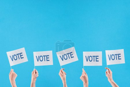 partial view of women holding flags with vote lettering on blue background