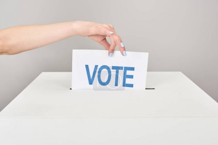 partial view of woman putting card with vote in box isolated on grey