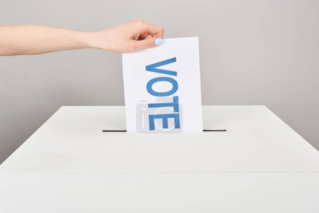 cropped view of woman putting card with vote in box isolated on grey