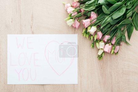 Photo pour Vue supérieure des fleurs et de la carte d'eustoma avec nous t'aimons le salut de maman sur la table en bois - image libre de droit