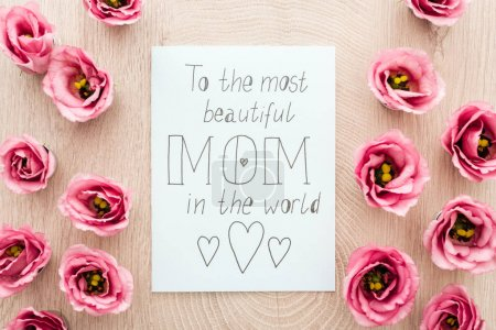 Photo for Top view of pink eustoma flowers and card with to the most beautiful mom in the world writing on table - Royalty Free Image