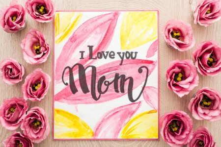 Foto de Top view of eustoma flowers and card with i love you mom words on wooden table - Imagen libre de derechos