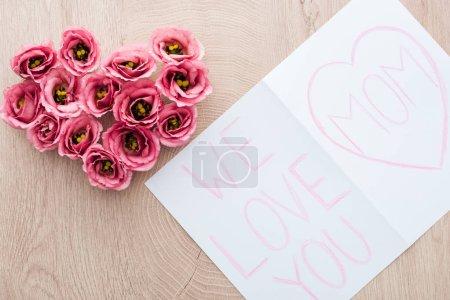 Photo pour Vue du haut des fleurs et de la carte en forme de coeur d'eustome avec nous t'aimons le lettrage de maman sur la table - image libre de droit