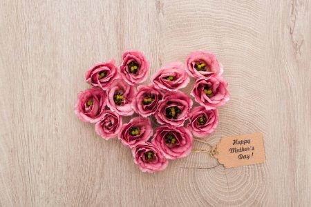 Photo pour Vue supérieure du signe de coeur fait des fleurs d'eustoma avec l'étiquette heureuse de papier de jour de mères sur la table en bois - image libre de droit