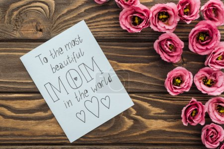 Photo for Top view of eustoma flowers and card with to the most beautiful mom in the world lettering on table - Royalty Free Image