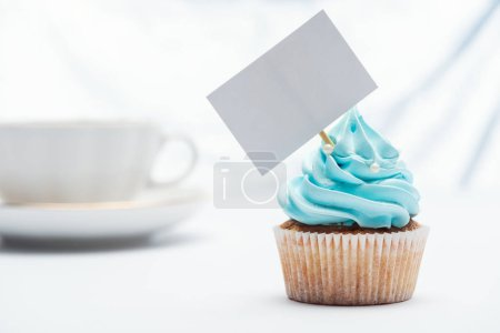 Photo for Selective focus of delicious blue cupcake decorated with sprinkles and blank card - Royalty Free Image