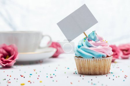 Photo for Selective focus of delicious cupcake decorated with sprinkles and blank card - Royalty Free Image