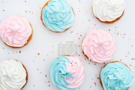 Photo for Top view of delicious white, pink and blue cupcakes with sprinkles Isolated On White - Royalty Free Image