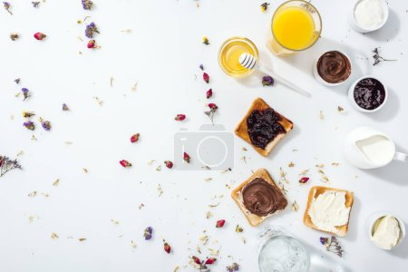 Photo pour Top view of tasty toasts with jam, chocolate cream and cream cheese near glasses of orange juice and water on white - image libre de droit