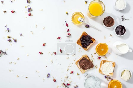 Photo for Top view of tasty toasts, bowls with jam and oranges near glasses of water and orange juice on white - Royalty Free Image
