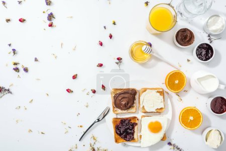 Foto de Top view of plate with toasts, jam and fried egg near glasses of water and orange juice on white - Imagen libre de derechos