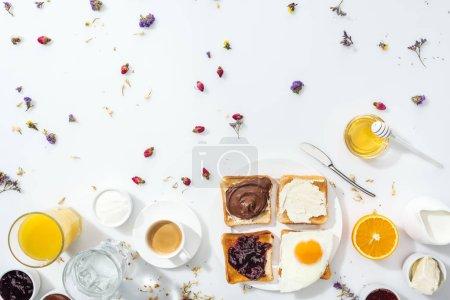 Blick von oben auf leckeres Frühstück mit Toasts und Marmelade in der Nähe von Gläsern mit Wasser und Orangensaft auf weiß