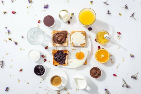 Photo pour Top view of tasty breakfast near glasses of water and orange juice on white - image libre de droit