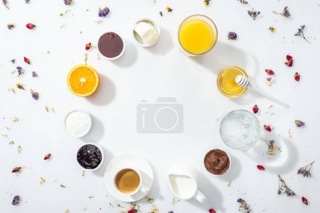Photo for Top view of bowls with jam, honey, chocolate cream and cream cheese near glasses with drinks on white - Royalty Free Image