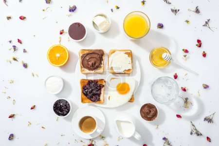 Photo for Top view of tasty toasts with jam, cream cheese, chocolate cream and friend egg near drinks on white - Royalty Free Image