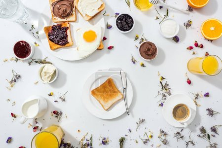 Photo for Top view of plates with tasty toasts and knife near drinks and oranges on white - Royalty Free Image
