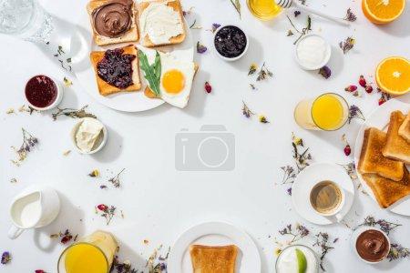 Photo pour Vue de dessus des assiettes avec des toasts savoureux près des boissons et des bols avec confiture sur blanc - image libre de droit