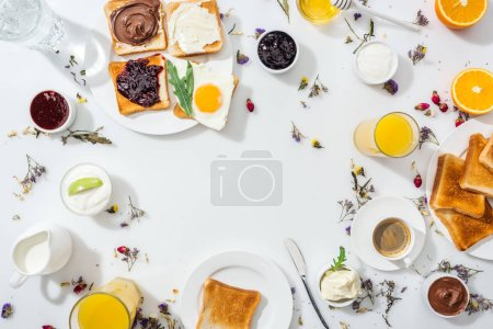 top view of plates with tasty toasts near drinks and bowls with jam and chocolate cream on white