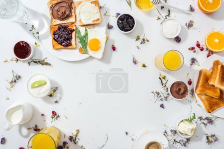 Photo for Top view of plate with tasty toasts near drinks and bowls with jam on white - Royalty Free Image