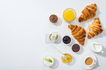 top view of tasty croissants near bowls with jam and orange juice on white