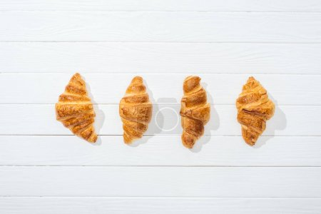 Photo for Flat lay of sweet and delicious croissants on white surface - Royalty Free Image