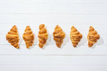 Photo pour Couche plate de croissants sucrés, savoureux et frais sur surface blanche - image libre de droit