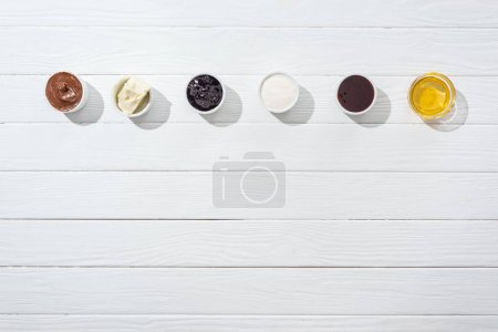 Photo for Top view of bowls with cream cheese, chocolate cream, sour cream, jam and honey on white - Royalty Free Image