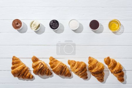 top view of bowls with cream cheese, chocolate cream, sour cream, jam and honey near fresh croissants on white