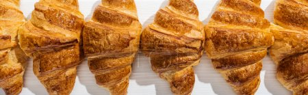 panoramic shot of sweet, tasty and fresh croissants on white surface
