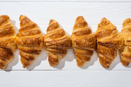 top view of sweet, tasty and fresh croissants on white surface
