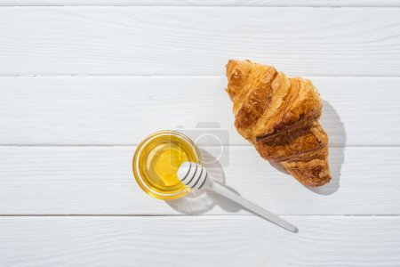 Photo for Top view of tasty and fresh croissant near glass bowl with honey and honey dipper on white surface - Royalty Free Image