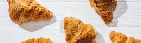panoramic shot of tasty and sweet croissants on white surface