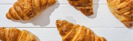 panoramic shot of delicious croissants on white surface
