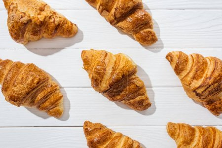 Photo for Flat lay of delicious and sweet croissants on white surface - Royalty Free Image