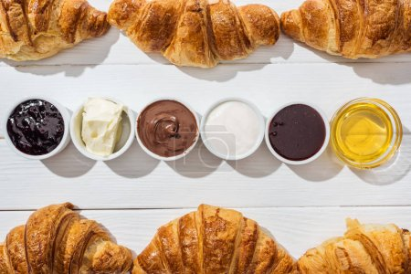 Photo for Top view of delicious croissants near bowls with cream cheese, chocolate cream, sour cream, jam and honey on white - Royalty Free Image