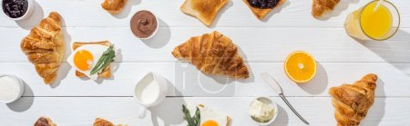 Photo for Panoramic shot of sweet croissants near tasty toasts with fried eggs on white - Royalty Free Image