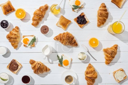 Photo for Top view of sweet croissants near tasty toasts with jam and fried eggs on white - Royalty Free Image