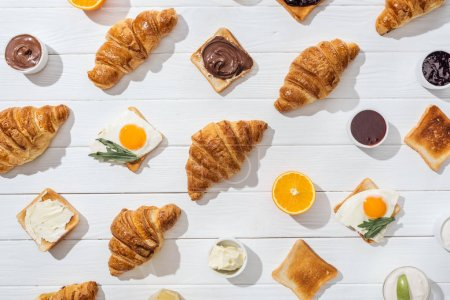 Photo for Top view of sweet croissants and tasty toasts with arugula leaves on friend eggs on white - Royalty Free Image