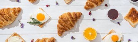 Photo for Panoramic shot of sweet croissants and tasty toasts near dried flowers on white - Royalty Free Image