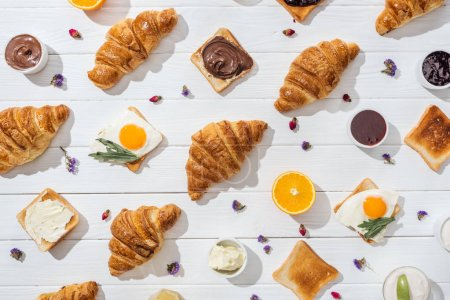 Photo for Top view of sweet croissants and tasty toasts with arugula leaves on friend eggs near dried flowers on white - Royalty Free Image