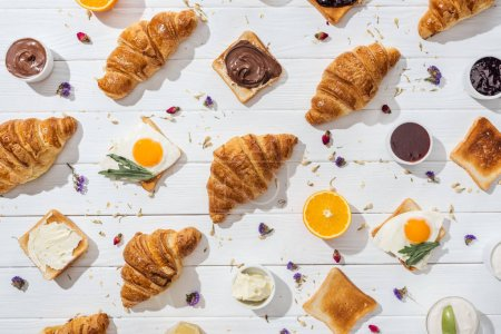 top view of sweet croissants and tasty toasts with fried eggs near dried flowers on white